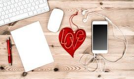 Kontorsarbetsplats med röd hjärta, tangentbord, minnestavlaPC, telefon Arkivfoton