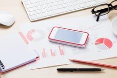 Kontorsarbetsplats med telefonen, diagram och notepaden arkivbilder