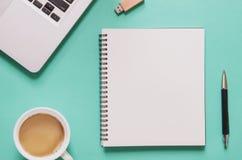 Kontorsarbetsplatsbegrepp Datorbärbar dator med den tomma anteckningsboken, kopp kaffe, penna, pråligt drev, på blå bakgrund arkivfoton