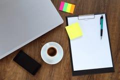 Kontorsarbetsplatsen med bärbara datorn, ilar telefon- och kaffekoppen på den wood tabellen Arkivfoton