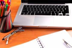 Kontorsarbetsplatsen med bärbara datorn och ilar telefonen på wood tabeller arkivfoto