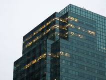 Kontorsbyggnad med ljus på skymning royaltyfri foto