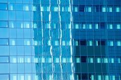 Kontorsbyggnad reflekterade i den glass fasaden av en annan kontorsbyggnad fotografering för bildbyråer