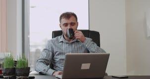 Kontorschefen har en stor dag i regeringsställning som framme dricker hans kaffe på hans arbetsställe av hans bärbar dator arkivfilmer
