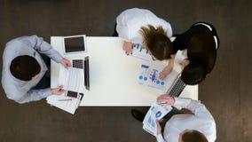Kontorscoworkers med bärbara datorer och rapporter som samlar för affärsmöte Fotografering för Bildbyråer