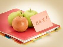 Kontorsdokument och äpplen; Äta arkivfoton