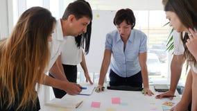 Kontorsfolk bredvid skrivbordet som diskuterar idénäringslivsutveckling arkivfilmer