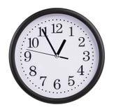 Kontorsklockan visar fem minuter till en timme Arkivbilder