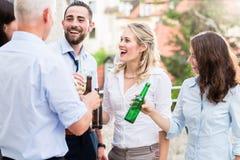 Kontorskollegor som dricker öl efter arbete arkivfoto