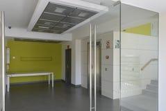 Kontorskorridor med exponeringsglas, keramisk golv och vit och gräsplanväggar Arkivfoto