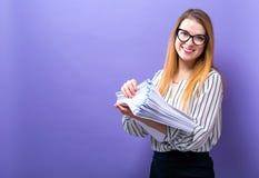Kontorskvinna med en bunt av dokument arkivbilder