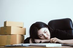 Kontorskvinna som sover över hennes arbete på skrivbordet Royaltyfri Foto