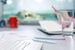 Kontorslivbegrepp - datorexponeringsglas av vatten och brevpapper arkivbilder