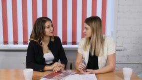 Kontorslivbegrepp Två nätta affärskvinnor som diskuterar framtida plan, idéer Smilie Angenäma sinnesrörelser Skjutit i 4k arkivfilmer