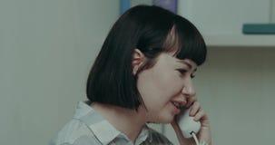Kontorsoperatörskvinnlign som talar på telefonen, har ett karismatiskt leende arkivfilmer
