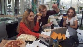 Kontorspersonal på avbrottet som sitter på tabellen som äter pizza och dricker söt sodavatten i glasflaskor stock video