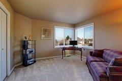 Kontorsrum i beige signal med den burgundy soffan Arkivbilder