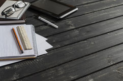 Kontorsskrivbord med affärsobjekt - öppen anteckningsbok, minnestavladator, exponeringsglas, linjal, blyertspenna, penna Fritt av Royaltyfri Foto