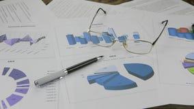 Kontorsskrivbord med affärsrapporten, exponeringsglas, pennan och mobiltelefonen panorama stock video