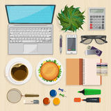 Kontorsskrivbord med anteckningsboken, glasögon, kaffe och bärbara datorn Arkivbilder