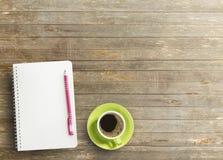 Kontorsskrivbord med anteckningsboken och kaffe Royaltyfri Foto