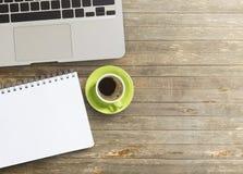 Kontorsskrivbord med anteckningsboken och kaffe Royaltyfria Bilder