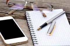 Kontorsskrivbord med anteckningsboken, reservoarpennan, glasögon och telefonen Royaltyfria Bilder