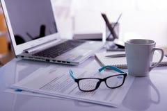 Kontorsskrivbord med bärbar datordatoren på det vita skrivbordet Arkivbild