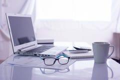 Kontorsskrivbord med bärbar datordatoren på det vita skrivbordet Royaltyfri Fotografi