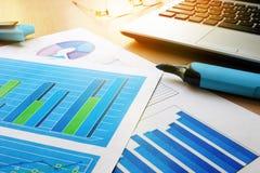 Kontorsskrivbord med den finansiella dokument, anteckningsboken och pennan Royaltyfri Foto