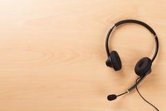 Kontorsskrivbord med hörlurar med mikrofon Tabell för service för appellmitt royaltyfria foton