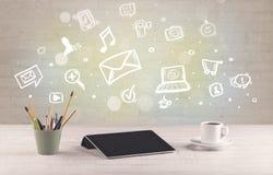 Kontorsskrivbord med kommunikationssymboler Royaltyfria Bilder