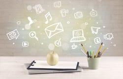 Kontorsskrivbord med kommunikationssymboler Arkivfoto