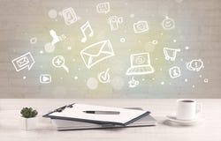 Kontorsskrivbord med kommunikationssymboler Royaltyfria Foton