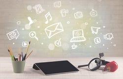 Kontorsskrivbord med kommunikationssymboler Arkivfoton
