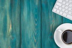 Kontorsskrivbord med kopieringsutrymme Digital apparater trådlöst tangentbord och mus på den blåa trätabellen med koppen kaffe, b arkivbild