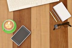 Kontorsskrivbord med koppen och telefonen för kaffe för anteckningsbokexponeringsglastangentbord vektor illustrationer