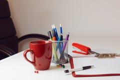 Kontorsskrivbord med olika objekt inklusive koppen, stol och stationärt för kaffe Arkivfoton