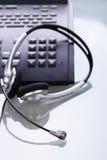 Kontorsskrivbord med telefon- och hörlurar med mikrofonobjekt Royaltyfria Foton