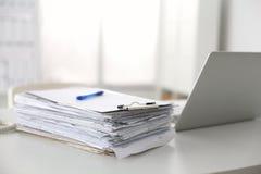 Kontorsskrivbord som en bunt av rapporter för datorpapper arbetar Royaltyfri Bild
