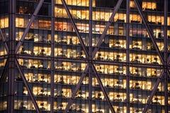 Kontorsskyskrapafönster på natten Arkivfoto