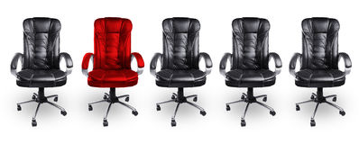 Kontorsstolar i svart och rött, står ut begrepp Royaltyfria Bilder