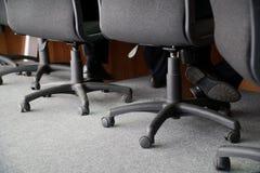 Kontorsstolar på hjul för arbetsuppgift på arbete Benen av två tjänstgörande som män sitter i stolar royaltyfria foton