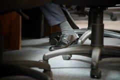 Kontorsstolar p? hjul f?r arbetsuppgift p? arbete Ben och tjänstgörande man för portfölj som sitter i en stol royaltyfria foton