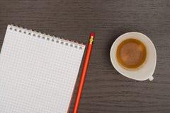 Kontorstabell med anteckningsboken, blyertspennan och koppen kaffe Arkivbilder