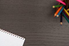 Kontorstabell med anteckningsboken och blyertspennor Arkivbild