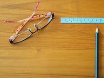 Kontorstabell med blyertspenna-, linjal- och ögonexponeringsglas royaltyfri foto