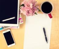 Kontorstabell med den digitala minnestavlan, det tomma arket för smartphone av papper och koppen kaffe ovanför sikt Royaltyfri Bild