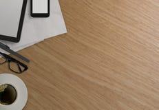 Kontorstabell med minnestavladatoren, mobiltelefonen och kaffekoppen Royaltyfri Foto