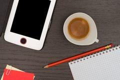 Kontorstabell med minnestavlan, anteckningsboken, blyertspennan och koppen kaffe Arkivfoton
